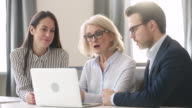 istock Experienced old female leader teaching mentoring business team with computer 1172551595