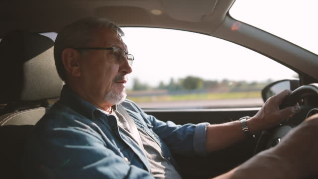 vídeos de stock, filmes e b-roll de o homem mais idoso experiente com vidros conduz um carro - veículo terrestre