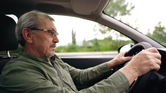 Experienced older man with glasses driving car on the highway video