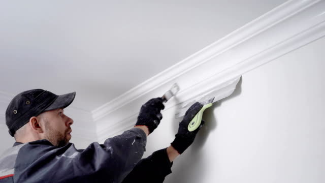 experienced painter is coloring plinth, fixing between ceiling and walls in a white, manual labor in a repair - painter stock videos and b-roll footage