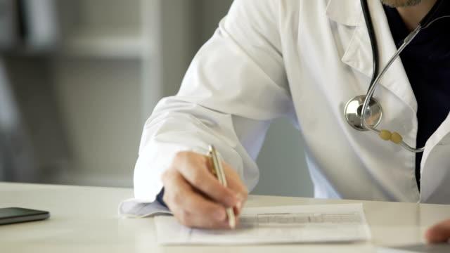 medico esperto che compila il modulo di richiesta di assicurazione sanitaria, assistenza sanitaria - prescrizione medica video stock e b–roll