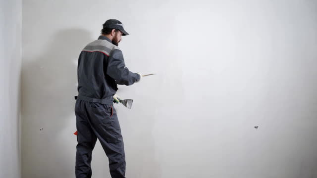 experienced repairman is plastering wall, using spatula, putty knife and white modern mortar, stuccoing - pezze di stoffa video stock e b–roll