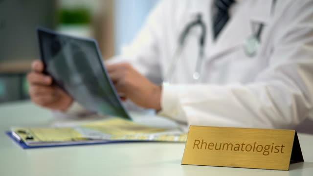 Experienced rheumatologist looking at x-ray image and writing down diagnosis video
