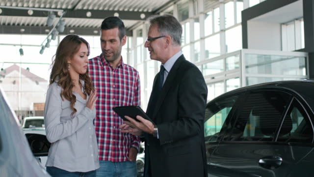 Experienced salesman selling a car to a young couple Experienced salesman selling a car to a young couple car shopping stock videos & royalty-free footage