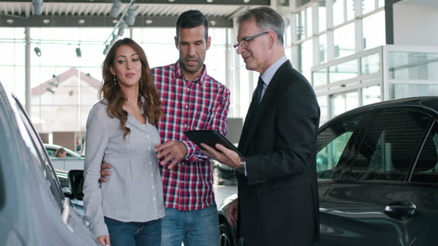 Experienced salesman selling a car to a young couple Experienced salesman selling a car to a young couple buying stock videos & royalty-free footage