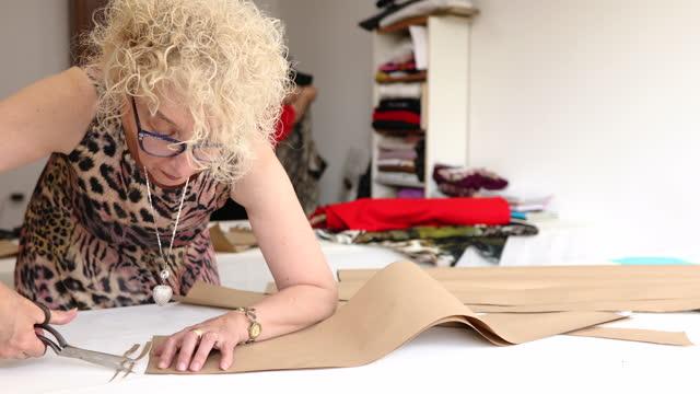 経験豊富な先輩女性仕立て屋は、彼女が後者がデザインのパターンとして使用できる茶色の紙を切り取る - disruptagingcollection点の映像素材/bロール