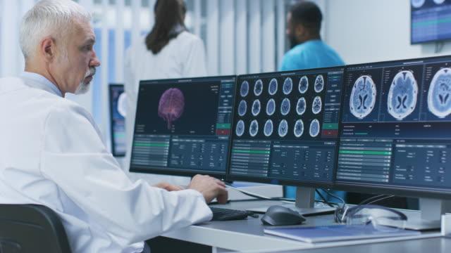vidéos et rushes de expérience scientifique travaillant avec ct / irm cerveau numériser des images sur un ordinateur personnel en laboratoire. neurologues / neuroscientifiques dans le centre de recherche médical de travail sur la cure de tumeur de cerveau. - image par résonance magnétique