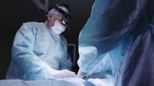 experienced surgeon stitching incision - cucitura video stock e b–roll