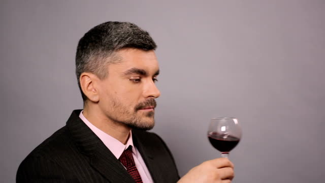 Experienced winemaker enjoying tasty red wine at cafe, ripe alcoholic beverage video