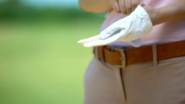 Experienced woman golfer wearing white glove, sport equipment, elite hobby