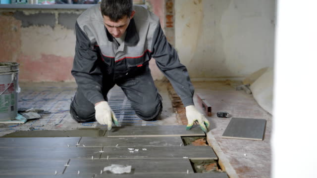 experienced worker is doing tiling work, is lying grey tiles on a floor in an office room with window - piastrella video stock e b–roll