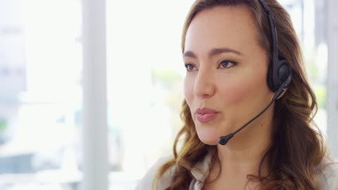 Expert customer support at your service 4k video footage of a young woman using a computer and headset in a modern office service stock videos & royalty-free footage