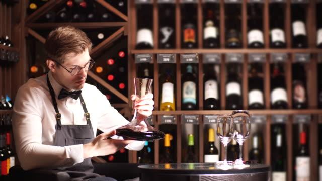 эксперт декантирования и заливки вина в стакан. обучение персонала для сомелье - декантер стоковые видео и кадры b-roll