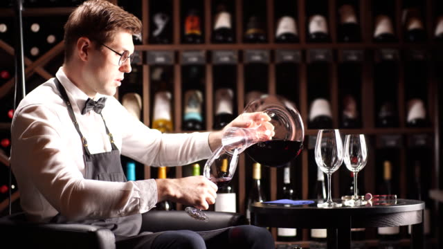 expert decanting and pouring wine into glass. staff training for sommelier - decanter video stock e b–roll