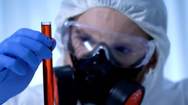 эксперт изучает колбу с токсикологическим веществом, центр по контролю заболеваний - expert стоковые видео и кадры b-roll