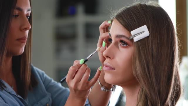 Expert female make-up artist putting makeup on her client