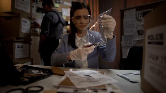 эксперт леди изучения кровавый нож с места убийства и писать результаты доклада - expert стоковые видео и кадры b-roll
