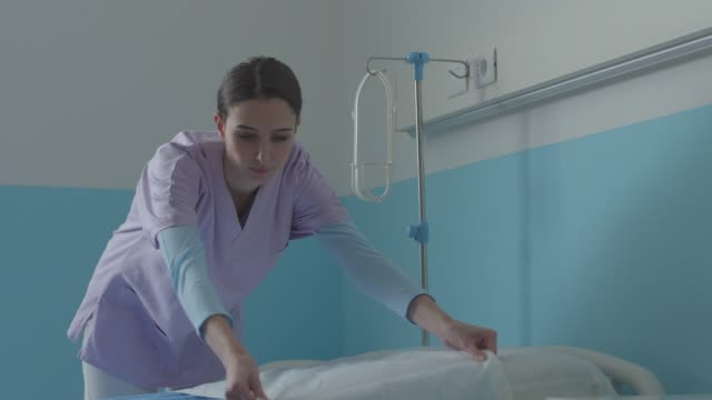expert nurse making the bed at the hospital - infermiera personale medico video stock e b–roll