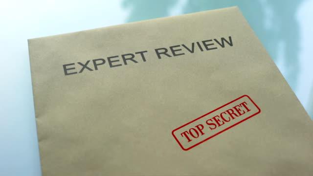 эксперт обзор совершенно секретно, ручная печать штамповки на папке с важными документами - expert стоковые видео и кадры b-roll
