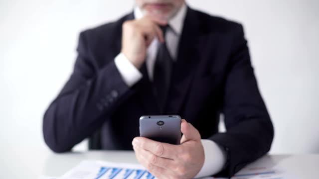 эксперт потирая подбородок, читая новостную ленту мобильного приложения о валютном рынке - expert стоковые видео и кадры b-roll