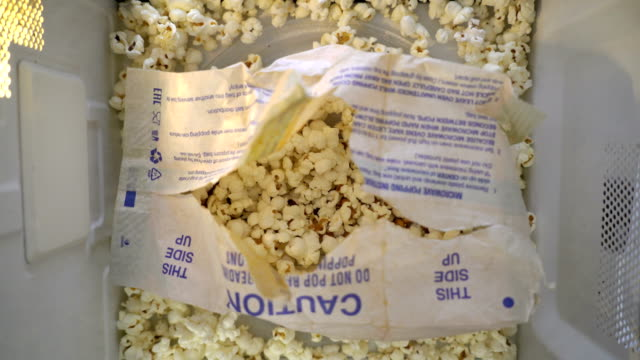 Exploded popped popcorn bag rotating in microwave