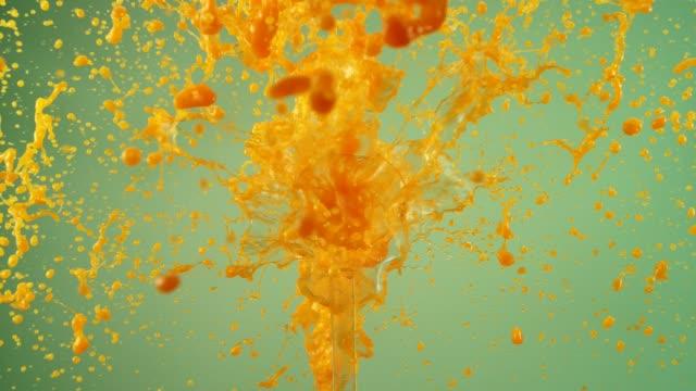 Exploding orange juice. Splashing in super slow motion