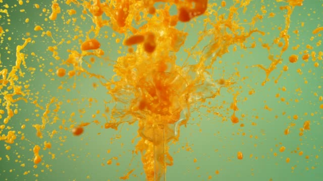 Exploding orange juice. Splashing in super slow motion Juice scattering on a pink background. Super slow motion, close up orange juice stock videos & royalty-free footage