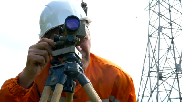 explorer in jumpsuit looks through dumpy level binocular