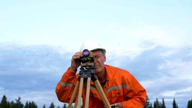 explorer looks through dumpy level binocular and types