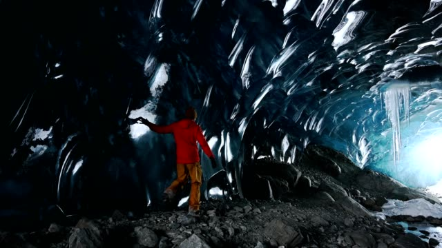 Exploring an ancient glacial ice cave Man exploring an ancient glacial ice cave in British Columbia cave stock videos & royalty-free footage