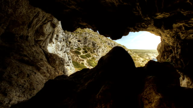 Exploring mountain cave. Time lapse. Inside cave. Looking at view. cave stock videos & royalty-free footage