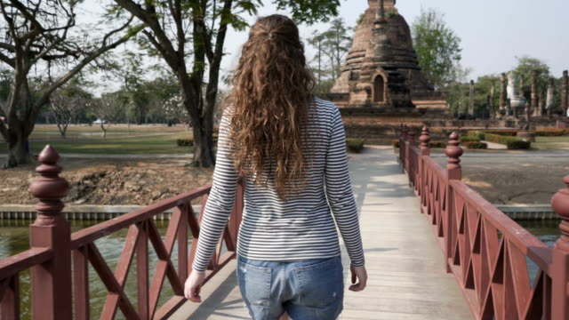 Exploring Thailand Rear view of a young caucasian female tourist exploring Thailand temples. sukhothai stock videos & royalty-free footage