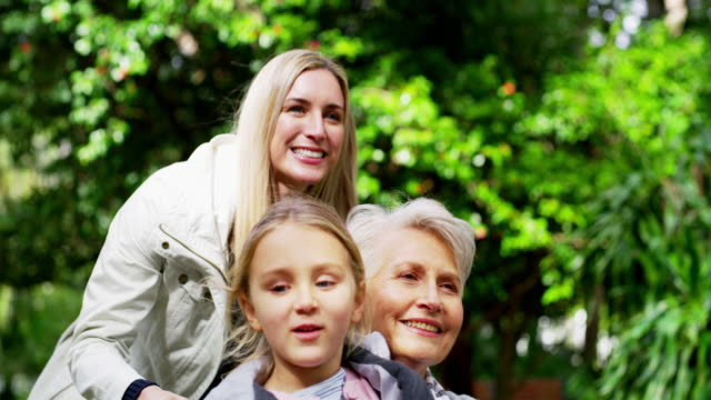 Exploring the gardens with her favourite girls 4k video footage of a senior woman in a wheelchair spending time with her family in the park pushing wheelchair stock videos & royalty-free footage