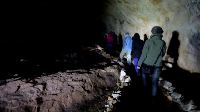 Exploring Group of young people exploring dark caves. archaeology stock videos & royalty-free footage