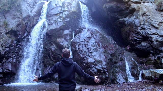 Exploring wilderness. Man admiring mountain waterfall video