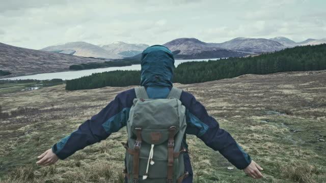 vídeos de stock e filmes b-roll de exploring wilderness. mountain landscape - man admires forest