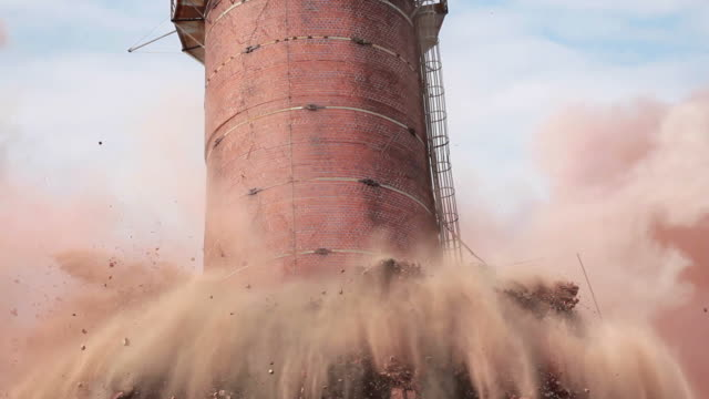 Explosion as smoke stack implodes and crumbles Tight shot of dynamite exploding as old chimney is demolished by implosion.  Smoke stack falls and crumbles into a cloud of dust. demolishing stock videos & royalty-free footage