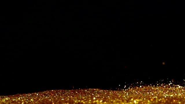 vídeos y material grabado en eventos de stock de explosión oro brillo polvo minúsculo reflejan la luz en el aire, big bang 3 veces - gastronomía fina