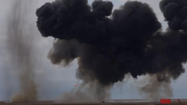 vidéos et rushes de explosion sur une plage fumée noire royaume-uni 4k - mitrailleuse
