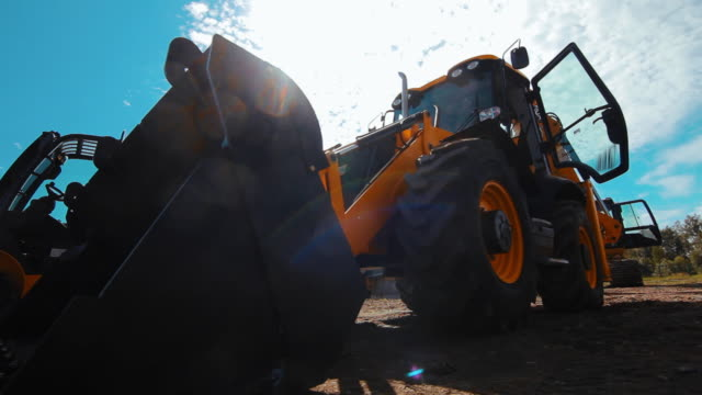exposition of new commercial construction equipment. big orange wheel loader - trattore video stock e b–roll