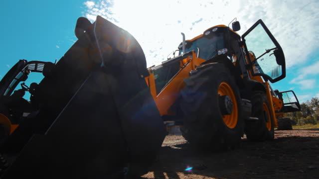 vídeos de stock e filmes b-roll de exposition of new commercial construction equipment. big orange wheel loader - trator