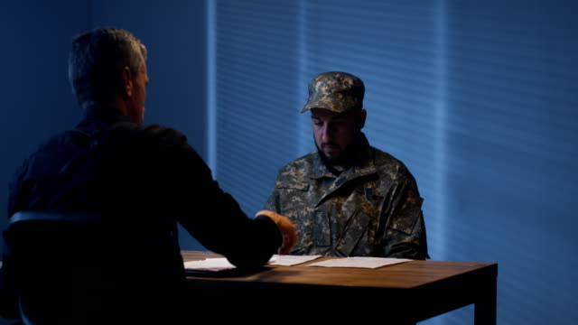 Expressive policeman examining military man in interview room Policeman laying few papers on table in front of detained suspect man in military uniform and asking questions police interview stock videos & royalty-free footage