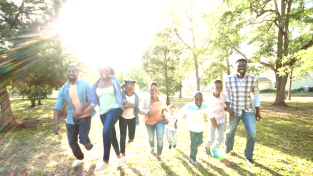 Extended African-American family running, playing video