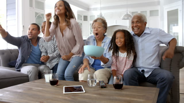 Extended Family Group At Home Watching Sports On TV Extended Family Group At Home Watching Sports On TV family watching tv stock videos & royalty-free footage