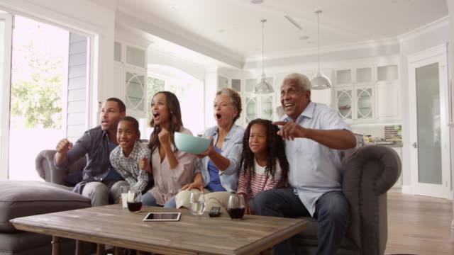 vídeos y material grabado en eventos de stock de familia grupo en su casa viendo televisión en el escalofriante r3d - family watching tv