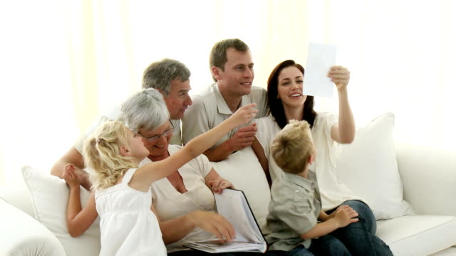 Extended family looking at a photo album video