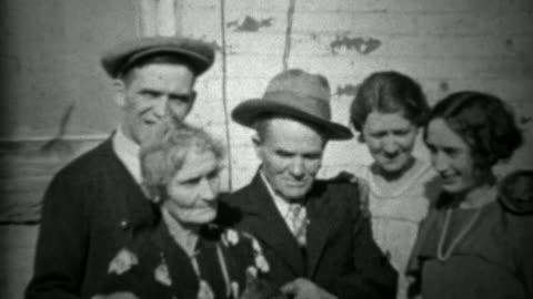 vidéos et rushes de 1933: famille élargie caresser voiture familiale en dehors de l'ère de dépression maison. - vintage