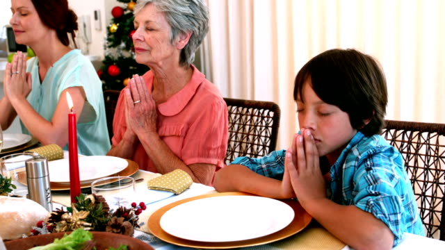 Extended family saying grace before christmas dinner video