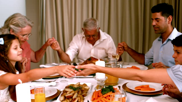 Extended family saying grace before dinner video