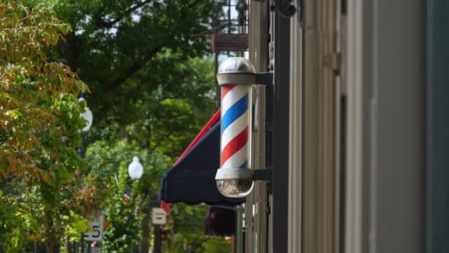 Exterior View of Barber Pole A daytime exterior view of a spinning barber pole outside an establishment in a small town. americana stock videos & royalty-free footage